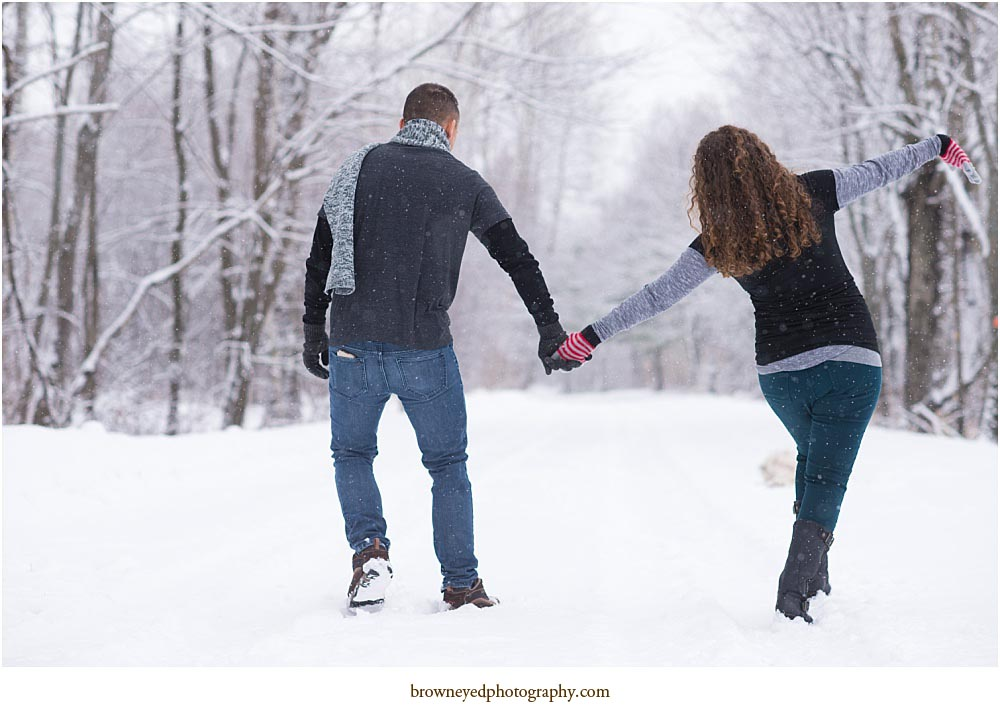 red head curly hair woman and dark haired man walking down winter path holding hands