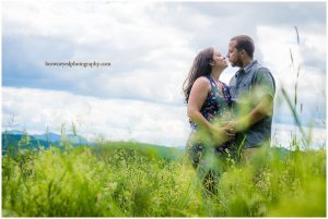 couple kissing in tall grass with mountains behind