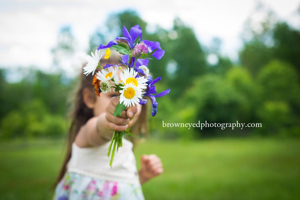 girl holding out bouquet of flowers